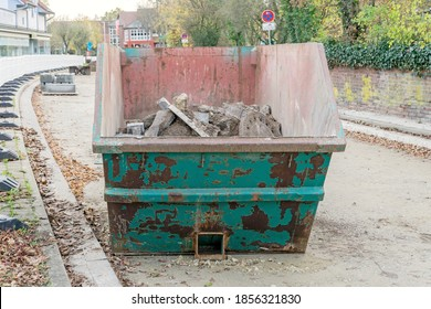 A skip container dumpster in roadworks building site with concrete rubble