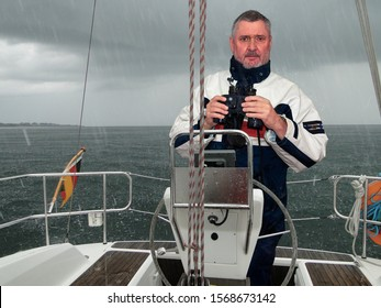 A skipper in the rain at the helm of a sailing yacht off the south coast of Sweden. The weather is very uncomfortable, the rain is enormous and hits the sea.