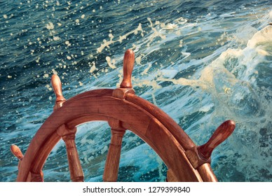 Skipper's wheel on an old ship, closeup. Wooden steering wheel on sea background with a motion waves in sunlight.