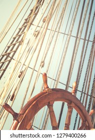 Skipper's wheel and sea tackles on the mast on a tall ship. Rigging ropes at blur background on a sailing vessel for your concept in marine style.