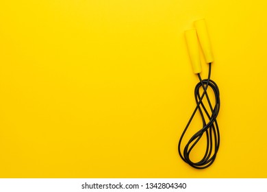 skipping rope with yellow handles on the yellow background with copy space