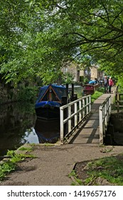 Skipton, Craven, Yorkshire Dales National Park, North Yorkshire, England, Britain, June 2019, narrow boats moored and couple with small dog walking on towpath of Leeds-Liverpool canal
