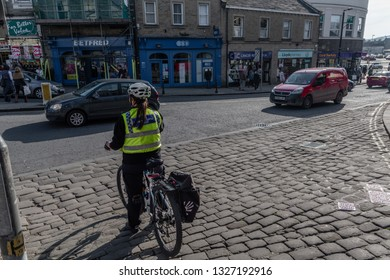 Skipton, England - 02 Feb 2019: Skipton police officer on bike making sure everything is right on high street round about