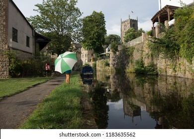 Skipton, England - 30 July 2018: Child with umbrella standing next to the Leeds Liverpool canal