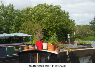 Skipton, North Yorks, UK - Circa August 2019:  Canal boat seen moored up on a famous English canal. Various plant pots can be seen on deck, the canal boat used as a permanent residence.