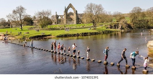 SKIPTON, UK - APRIL 21, 2018: People crossing the River Wharfe by means of stepping stones, Bolton Abbey, North Yorkshire, UK
