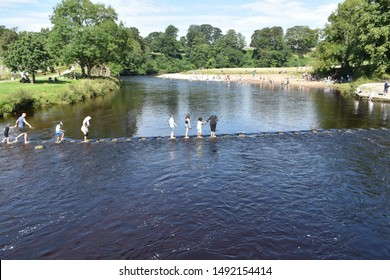 SKIPTON, UK - AUGUST 30, 2019: People crossing the River Wharfe by means of stepping stones, Bolton Abbey, North Yorkshire, UK