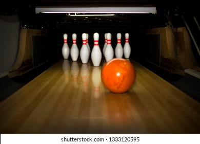 skittle and bowling ball on wooden floor