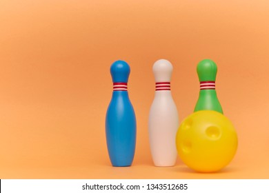 skittles and a ball for playing bowling on a peach background with copy space. Kids toys.