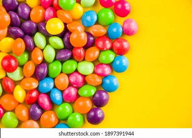 Skittles candy on the yellow table, colorful sweet candy background, high angle view