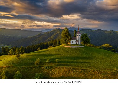 Skofja Loka, Slovenia - Aerial view of the beautiful hilltop church of Sveti Tomaz (Saint Thomas) with an amazing colorful sunset and the Julian Alps at background at summer time
