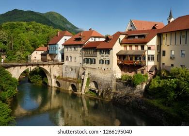 Skofja Loka, Slovenia - May 14, 2017: Stone Capuchin bridge and historic houses reflected in the Selca Sora river in Skofja Loka village Slovenia