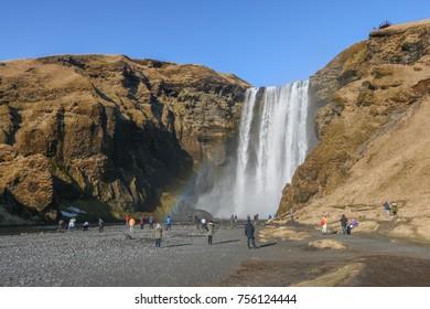SKOGAFOSS, 11 MAY 2017 - Tourists were scatterred around the huge Skogafoss waterfall. Visible rainbow near the waterfall.