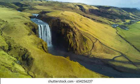 Skogafoss waterfall from aerial view behind green and yellow grass cliff, South Iceland