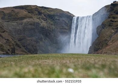 Skogafoss Waterfall In Iceland. Blue Sky. Water Spray. Evening Photo Shoot.