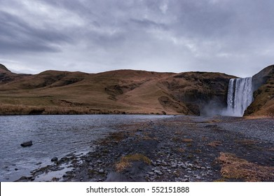 Skogafoss Waterfall In Iceland with Cloudy Blue Sky and Landscape