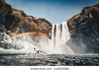 Skogafoss waterfall in Iceland with rainbow on a sunny day with blue sky.