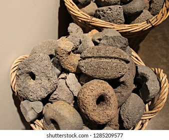 Skogar Museum, Iceland - December 1, 2013: Icelandic 16th century worn out farm stone tools, partially in fragments such as hammer heads, stockfish hammers and sinkers collected inside a straw basket