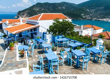 Skopelos / Greece - September 10, 2014: An old restaurant on hill in Skopelos town with outdoor seats from woodware blue painted furnitures and sea views