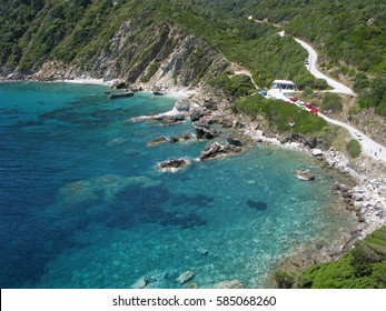 Skopelos island, Greece. Panorama, aerial view from church of Agios Ioannis. Scenic bay with transparent turquoise water. On image also mountain road, people and cars.