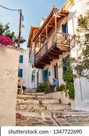 Skopelos Island, Greece. September 2018: Grandma and grandpa with a newspaper sitting at the old houses with a balcony in the summer on a narrow street of the island of Skopelos in Greece