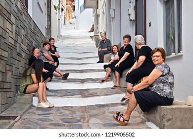 SKOPELOS ISLAND, NORTHERN SPORADES, GREECE- June 20, 2018. Ladies sitting and chatting in a stairway of Skopelos town.