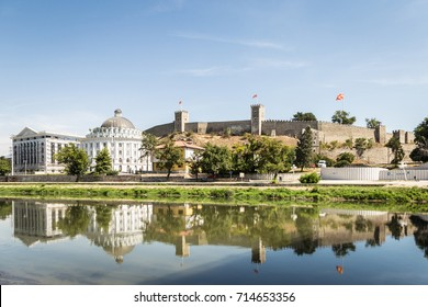 Skopje cityscape with the famous Skopje citadel and the Kale fortress reflecting in the water of the Vardar river on a sunny summer day in Macedonia capital city in the Balkans.