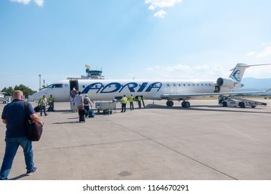 Skopje, Macedonia - August 25 2018: Passengers board Adria Airways Bombardier CRJ-900 passenger jet at Skopje Airport to Ljubljana. Adria is local carrier connecting short flights to the Balkans.