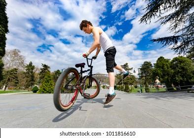 Skopje, Macedonia - circa Apr, 2013: Below view of bmx cyclist jumping against the sky