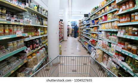 Skopje, Macedonia - circa Mar, 2018: Shopping Cart View moving between a Supermarket Aisle and Shelves