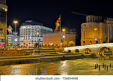SKOPJE, MACEDONIA (FYROM) - AUGUST 13 - Night view of the main Macedonia Square, reconstructed during Skopje 2014 project, with the old Stone Bridge across the Vardar River on August 13, 2017