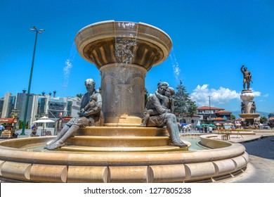 Skopje, Macedonia - July 2nd 2018 - Tourist and locals walking near a high statue with a water fountain in a blue sky day in Skopje