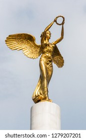 Skopje, Macedonia - June 10, 2013: Golden winged goddess woman holding wreath is a top part of the monument Fallen Heroes of Macedonia, located in the Zena Borec park in Skopje, Macedonia