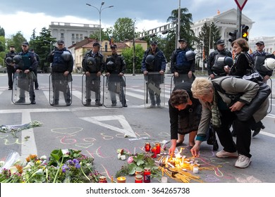 SKOPJE, MACEDONIA - MAY 11, 2015: Street protest against prime minister Nikola Gruevski's government. Two elderly women lighting the candles in front of the policemen.