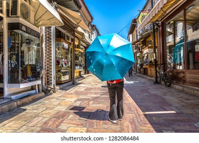 Skopje, Macedonia - May 31st 2018 - A tourist with a blue umbrella walking in the old town of Skopje