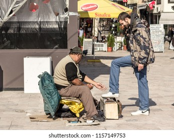 SKOPJE, MACEDONIA - OCTOBER 10. 2015: Shoeshiner polishing the shoes of a white young man in the Skopje bazar in the capital city of Macedonia