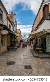 SKOPJE, MACEDONIA - SEPTEMBER 22, 2016: Narrow street in the old parts of Skopje September 22, 2016. Cafe, stores and restaurants on the side with people walking by on the street.