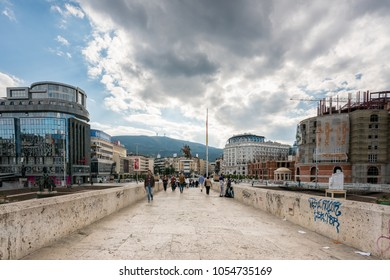 SKOPJE, MACEDONIA - SEPTEMBER 22, 2016: Perspective view of people walking on a stone bridge in the city center of Skopje September 22, 2016. Modern buildings and construction on booth sides.