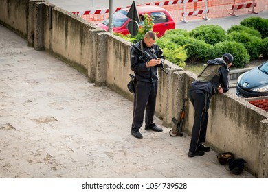 SKOPJE, MACEDONIA - SEPTEMBER 22, 2016:  Two armed security officers taking a break on a stone bridge in the city center of Skopje Macedonia September 22, 2016. Incidental people in the background.