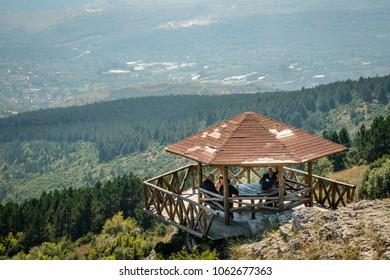 SKOPJE, MACEDONIA - SEPTEMBER 23, 2016: Mountain view of five people sitting at a picnic rest area overlooking the mountains in Skopje Macedonia September 23, 2016.
