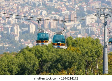Skopje, Macedonia - September 24, 2018: Cable car elevator with city view to Skopje in background. Gondola cabin lift from Vodno mountain