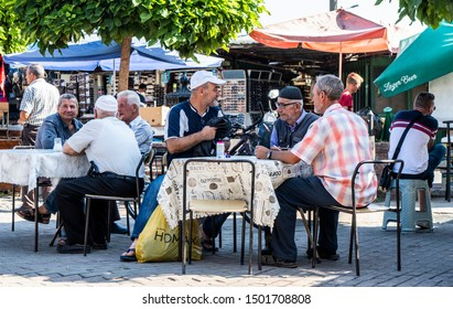 Skopje / North Macedonia - 20 Aug 2019: A group of elderly men sit for a coffee and a chat at tables under shady trees and umbrellas at an outside cafe in the Old Bazaar area of the city.