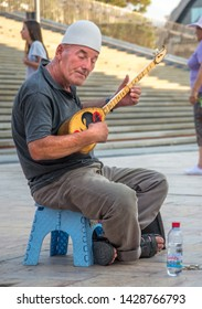 SKOPJE,MACEDONIA-AUGUST 29,2018:Elderly man plays music on a trditional stringed instrument,sitting outside in the Old Bazaar area of Skopje.