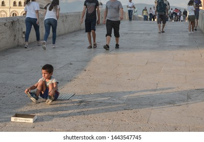 SKOPJE,NORTH MACEDONIA/AUGUST 22 2018:Young boy sits on Stone Bridge asking for money from passers by.Skopje,2018.