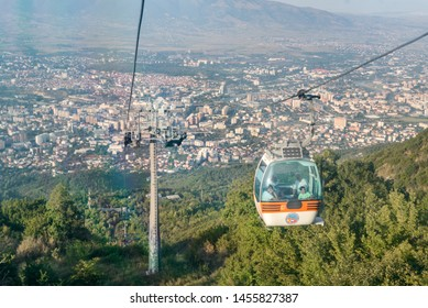 SKOPJE,REPUBLIC OF NORTH MACEDONIA-AUGUST 24 2018:Cable carwith tourists climbs up to Millennium Cross,Vodno Mountain,overlooking Skopje city at 3500 foot summit.