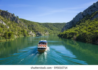 Skradin Croatia Europe. Boat on a river. Nature and landscape photo. Mountains, green forest and blue clear sky. Beautiful warm summer day. Relaxing and peaceful vacation.