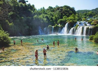 SKRADIN, CROATIA - JULY 8, 2018: Tourists bathing in a waterfall in Krka National Park at Skradin city in Croatia