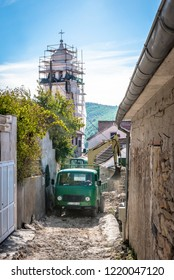 SKRADIN, CROATIA - OCTOBER 2, 2018: Construction machinery (truck and excavator) for the repair of the church tower in Skradin town, Croatia