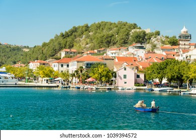 SKRADIN, CROATIA, SEPTEMBER 28, 2017: Fischer and tourist in the beautiful town of Skradin