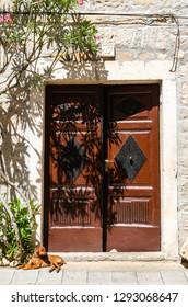 Skradin, Dalmatia / Croatia - 21 07 2014: Old stone house with brown doors, dog lying at the door. Croatian town Skradin